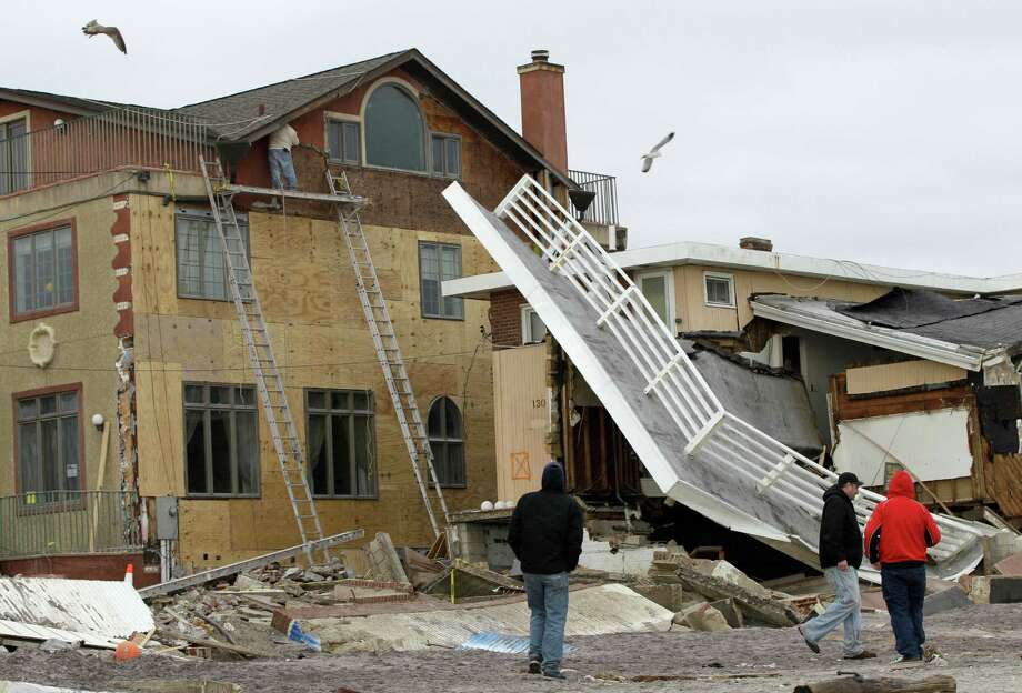 Spectators walk past a destroyed house as a worker repairs damage to an adjacent house in the Belle Harbor neighborhood of the Rockaways, Monday, Nov. 19, 2012, in New York. The house at right was tagged unsafe to enter or live in by the New York City Department of Buildings. Photo: Kathy Willens, AP / AP