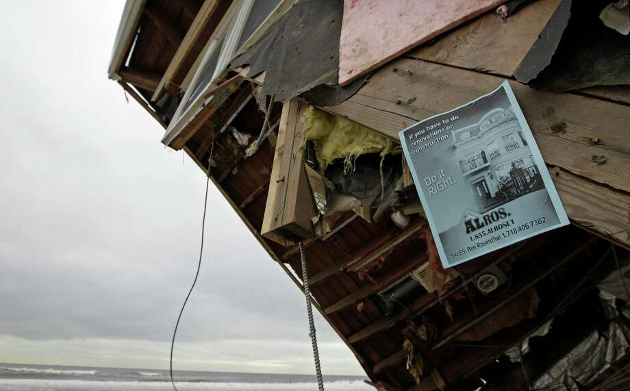 An advertisement for renovation and construction is attached to a red-tagged home in the Belle Harbor neighborhood of the Rockaways, Monday, Nov. 19, 2012, in New York. The New York City Department of Buildings inspected the house and ruled it unsafe to enter or live in. Photo: Kathy Willens, AP / AP