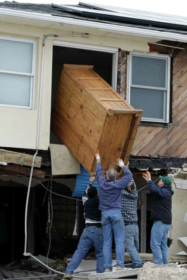 Friends of homeowner Jeffrey Gitter remove a wooden storage chest from his destroyed house in the Belle Harbor neighborhood of the Rockaways, Monday, Nov. 19, 2012, in New York. The men said the chest was the only thing he was able to salvage from his house, destroyed during Superstorm Sandy three weeks ago. Photo: Kathy Willens, AP / AP