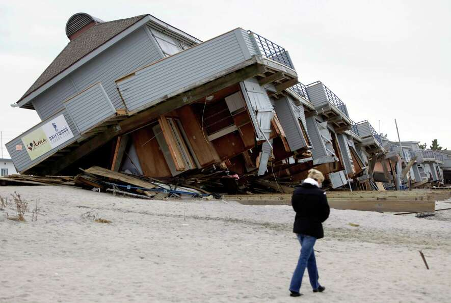 A woman walks past a cabana complex on the beach pulled off its foundations by Superstorm Sandy in S