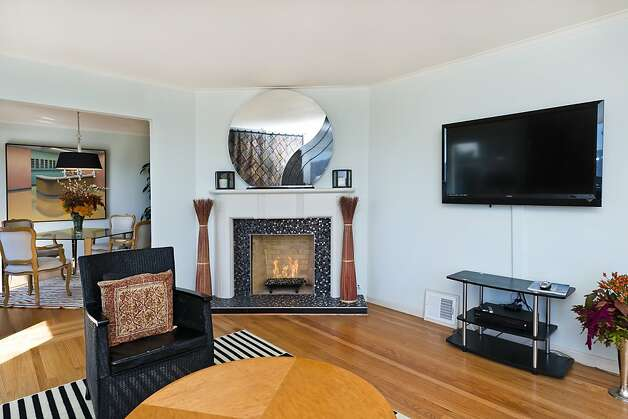 The living room has hardwood floors, a fireplace and powder-blue walls. Photo: Olga Soboleva