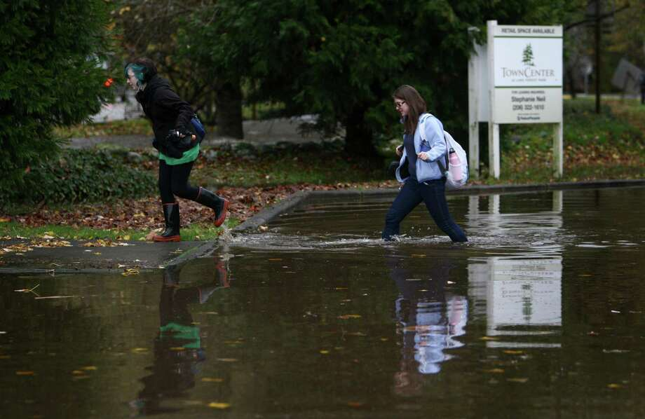 Pedestrians make their way across a flooded section of Bothell Way NE in Lake Forest Park during a significant rainfall on Monday, November 19, 2012. Photo: JOSHUA TRUJILLO / SEATTLEPI.COM
