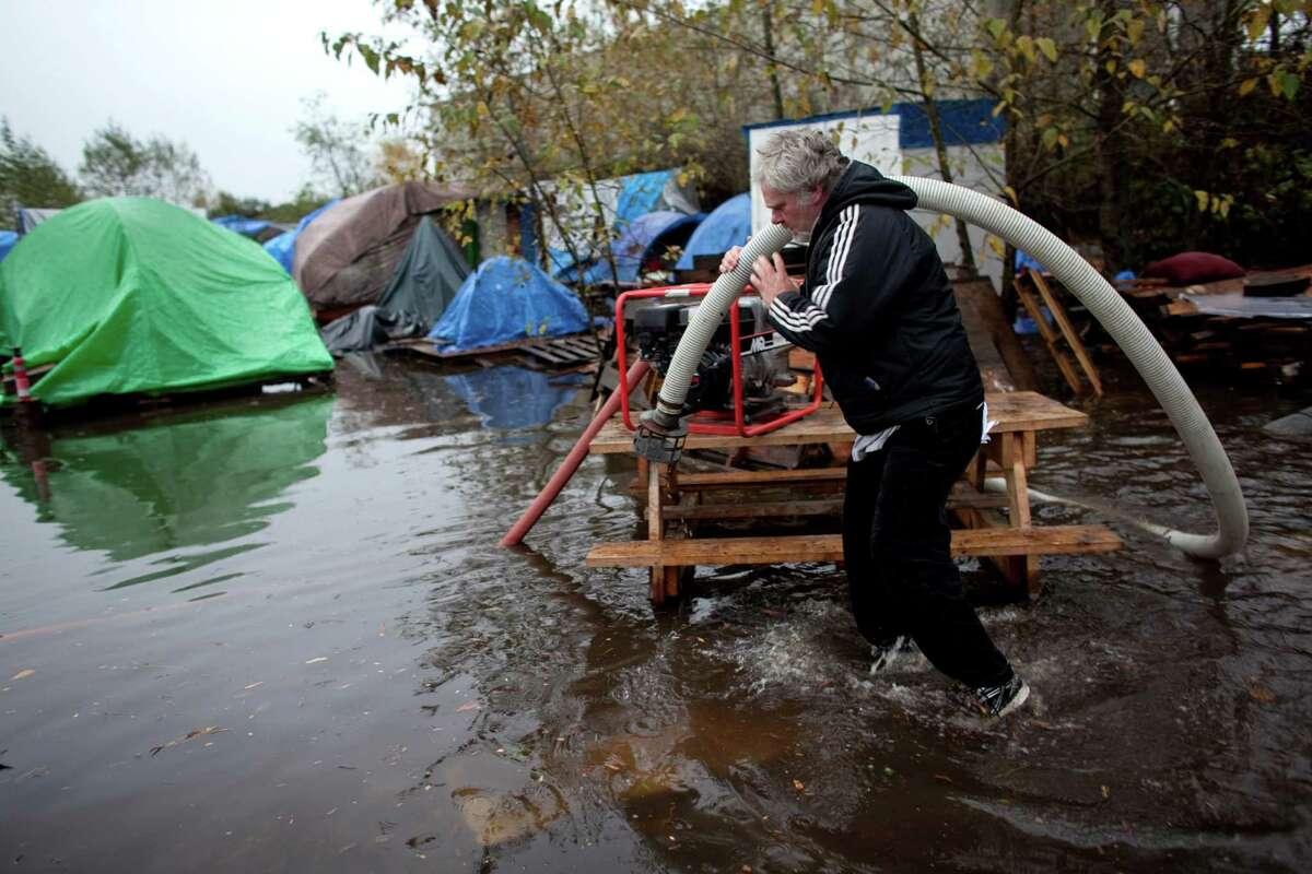 Resident George Sidwell repositions a heavy duty pump on loan after record rainfall flooded Seattle's Nickelsville homeless camp at 7116 West Marginal Way South. Tents and the pallets they rested on were floating after the camp filled with up to one foot of water after Monday's record rain. The camp is in need of dry blankets (fleece), new tarps, tents, dry clothing, and gas to power the pumps and generators. Organizers welcome the donations at the camp, 7116 West Marginal Way South.