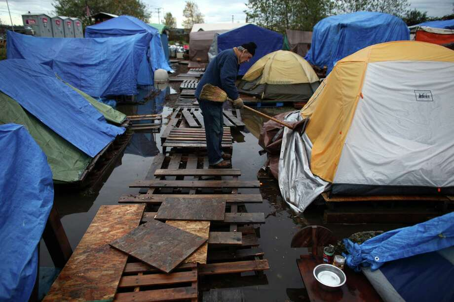 Resident Jim Morgan works to help water flow toward a pump after record rainfall flooded Seattle's Nickelsville homeless camp at 7116 West Marginal Way South. Tents and the pallets they rested on were floating after the camp filled with up to one foot of water after Monday's record rain. The camp is in need of dry blankets (fleece), new tarps, tents, dry clothing, and gas to power the pumps and generators. Organizers welcome the donations at the camp, 7116 West Marginal Way South. Photo: JOSHUA TRUJILLO / SEATTLEPI.COM