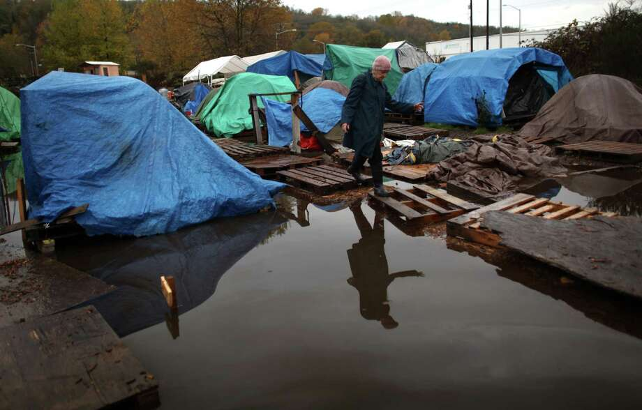 A Nickelsville resident walks across a makeshift bridge after record rainfall flooded Seattle's Nickelsville homeless camp at 7116 West Marginal Way South. Tents and the pallets they rested on were floating after the camp filled with up to one foot of water after Monday's record rain. Photographed on Tuesday, November 20, 2012. The camp is in need of dry blankets (fleece), new tarps, tents, dry clothing, and gas to power the pumps and generators. Organizers welcome the donations at the camp, 7116 West Marginal Way South. Photo: JOSHUA TRUJILLO / SEATTLEPI.COM