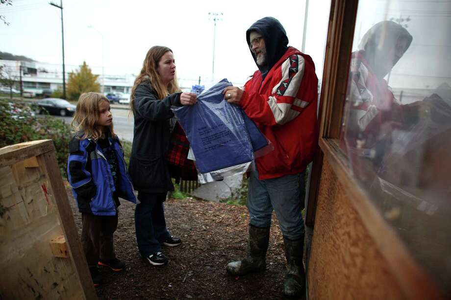 Stan Combes, 8, celebrates his 8th birthday by donating supplies with his mom Kami to Niclesville resident Steve Westfall after they learned on the Internet that record rainfall flooded Seattle's Nickelsville homeless camp at 7116 West Marginal Way South. Tents and the pallets they rested on were floating after the camp filled with up to one foot of water after Monday's record rain. The camp is in need of dry blankets (fleece), new tarps, tents, dry clothing, and gas to power the pumps and generators. Organizers welcome the donations at the camp, 7116 West Marginal Way South. Photo: JOSHUA TRUJILLO / SEATTLEPI.COM