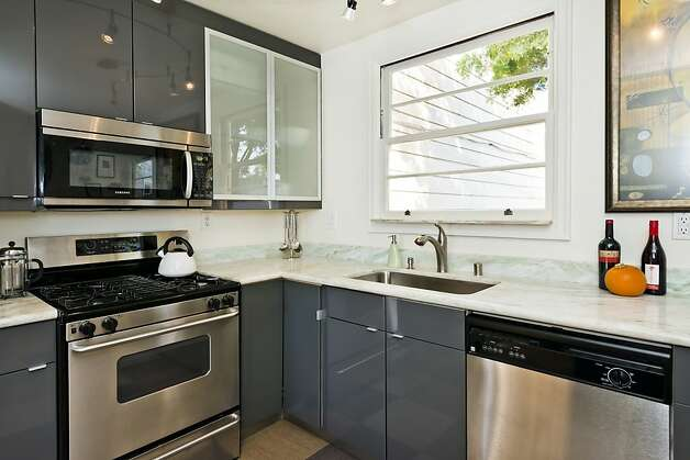 The kitchen is contemporary and includes stainless steel appliances. Photo: Olga Soboleva