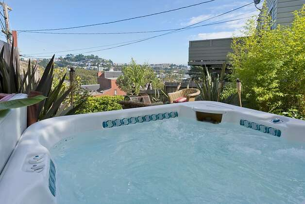 Built in 1948, this three-bedroom S.F. home has a hot tub in its sizable yard that offers great views. Photo: Olga Soboleva