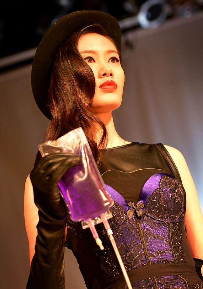 "Poison IV:A model carries an intravenous accessory during Greenpeace's ""Toxic Threads - The Big Fashion Stitch-up"" show in Beijing. Greenpeace says a months-long global investigation into some of the world's top-selling fashion houses revealed that nearly two-thirds of the clothing tested positive for hormone-disrupting dyes that release cancer-causing substances. Photo: Mark Ralston, AFP/Getty Images"