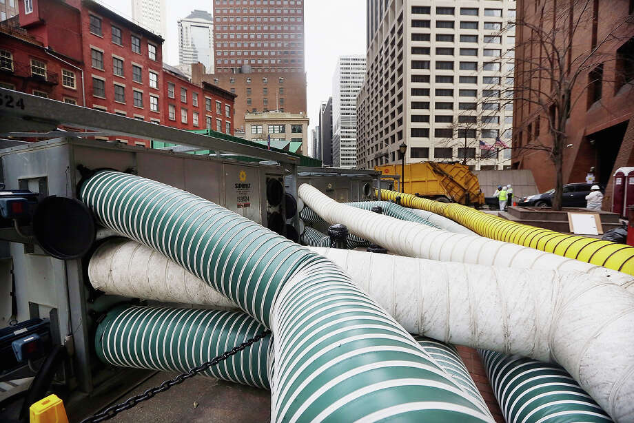 NEW YORK, NY - NOVEMBER 19:  Tubes carry hot air being pumped into a Financial District building that flooded in an attempt to dry out the building following Superstorm Sandy on November 19, 2012 in New York City. Many of the office towers in the low lying Financial District which flooded remain closed due to damage to heating and electrical infrastructure.  Many other buildings in the area are being powered by generators. Photo: Mario Tama, Getty Images / 2012 Getty Images