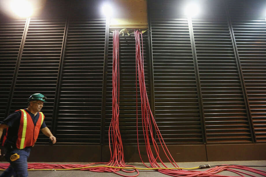 NEW YORK, NY - NOVEMBER 19:  A worker walks past temporary cables running from generators into a Financial District building in an area that flooded during Superstorm Sandy on November 19, 2012 in New York City. Many of the office towers in the low lying Financial District which flooded remain closed due to damage to heating and electrical infrastructure.  Many other buildings in the area are being powered by generators. Photo: Mario Tama, Getty Images / 2012 Getty Images