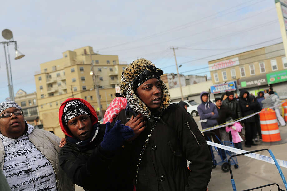 NEW YORK, NY - NOVEMBER 19:  Women wait in line at a food distribution site in the heavily damaged Rockaway neighborhood where a large section of the iconic boardwalk was washed away on November 19, 2012 in the Queens borough of New York City. Three weeks after Superstorm Sandy slammed into parts of New York and New Jersey, thousands are still without power and heat. Photo: Spencer Platt, Getty Images / 2012 Getty Images