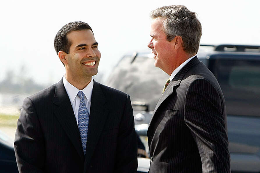 Former Florida Gov. Jeb Bush, right, talks with his son, George P. Bush.