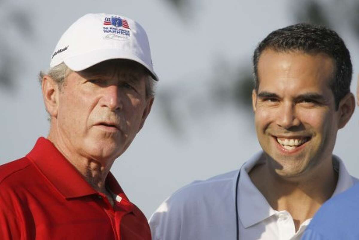George P. Bush, right, stands with his uncle former President George W. Bush, left, during the Bush Center Warrior Open in Irving, Texas.