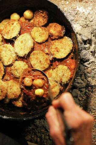 Bill Perry, who is a vegetarian, pours sauce over fried green tomatoes and eggplant to finish his award-winning Green Egg I Am I Am Ragu. Photo: Jennifer Whitney, For The Express-News / © Jennifer Whitney