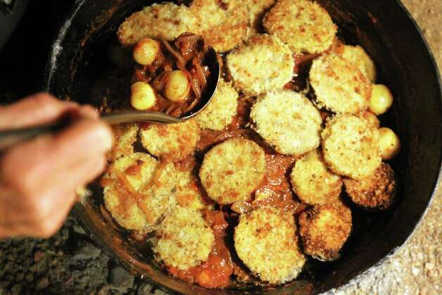 Bill Perry pours sauce over fried green tomatoes and eggplant to finish his Green Egg I Am I Am Ragu during the Fifth Annual Wang Dang Doodle Dutch Oven Cook-Off at the home of Cheryl and John Schilhab near Boerne, Saturday, Nov. 17, 2012. Perry won the people's choice award in the competition. Photo: Jennifer Whitney, For The Express-News / © Jennifer Whitney