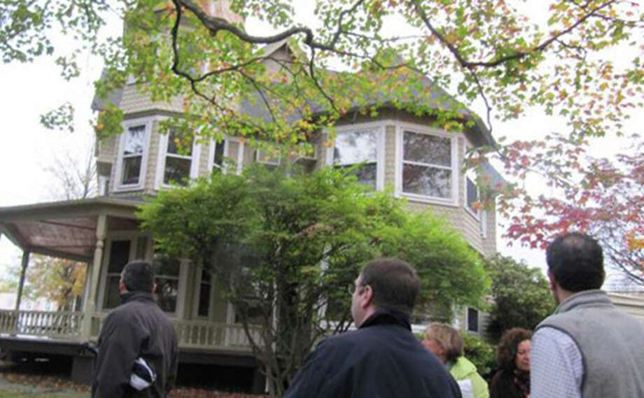 David Waldman, right, a partner in Bedford Square Associates, last year joined members of the Planning and Zoning Commission for a tour of downtown properties where the developers are proposing a multi-faceted project, including the Church Lane site of this 1890 Queen Anne Victorian house. Photo: File Photo / Westport News