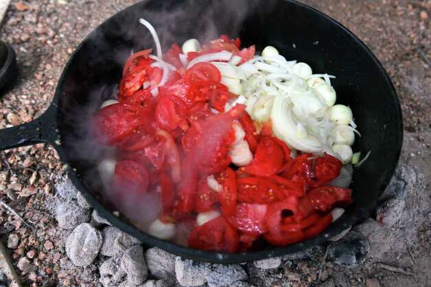 Fresh tomatoes and onions make up the beginning of the sauce for Bill Perry's Green Egg I Am I Am Ragu during the Fifth Annual Wang Dang Doodle Dutch Oven Cook-Off at the home of Cheryl and John Schilhab near Boerne, Saturday, Nov. 17, 2012. Perry won the people's choice award in the competition. Photo: Jennifer Whitney, For The Express-News / © Jennifer Whitney