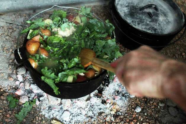 Kale is added to a chicken kale stew with cannellini beans during the Fifth Annual Wang Dang Doodle Dutch Oven Cook-Off at the home of Cheryl and John Schilhab near Boerne, Saturday, Nov. 17, 2012. Photo: Jennifer Whitney, For The Express-News / © Jennifer Whitney