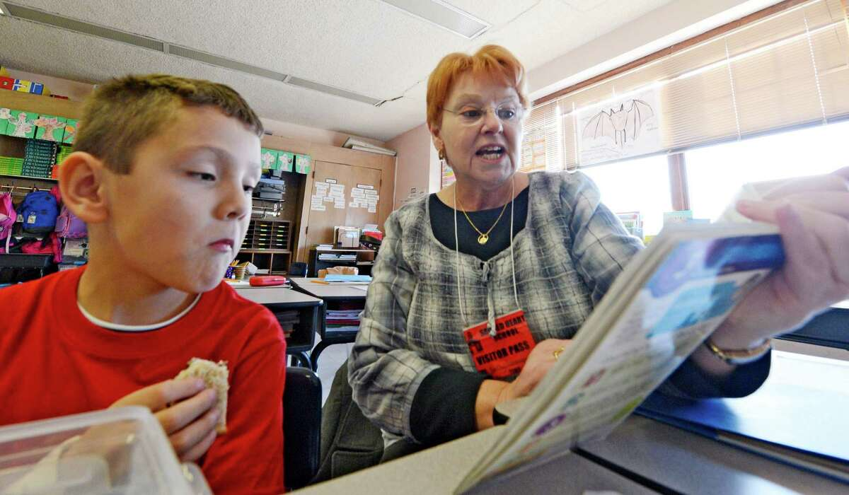 """Kathie Lonergan reads to Aiden Somerville during the """"Everybody Wins!"""" Power Lunch, a Literacy Volunteers of Rensselaer County program, in which elementary school children are paired with volunteer mentors who read to them during their lunch period at Sacred Heart School in Troy, N.Y. Nov 13, 2012. (Skip Dickstein/Times Union)"""