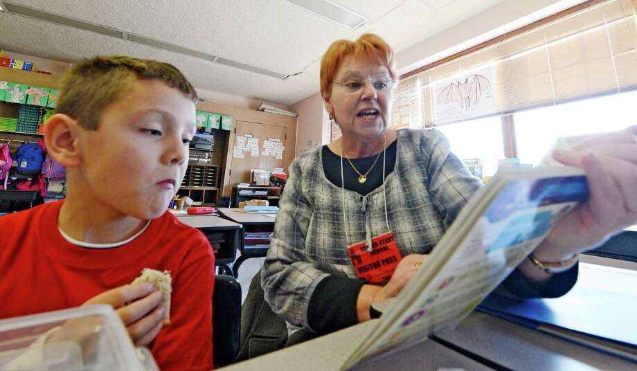 "Kathie Lonergan reads to Aiden Somerville during the ""Everybody Wins!"" Power Lunch, a Literacy Volunteers of Rensselaer County program, in which elementary school children are paired with volunteer mentors who read to them during their lunch period at Sacred Heart School in Troy, N.Y. Nov 13, 2012.     (Skip Dickstein/Times Union) Photo: Skip Dickstein / 00020101A"