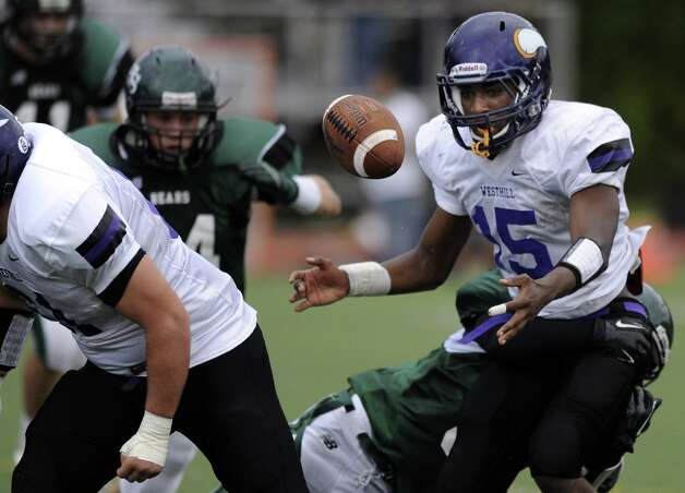 Westhill's Davell Cotterell loses control of the ball during Saturday's football game against Norwalk High School at Westhill High School on September 29, 2012. Photo: Lindsay Niegelberg / Stamford Advocate