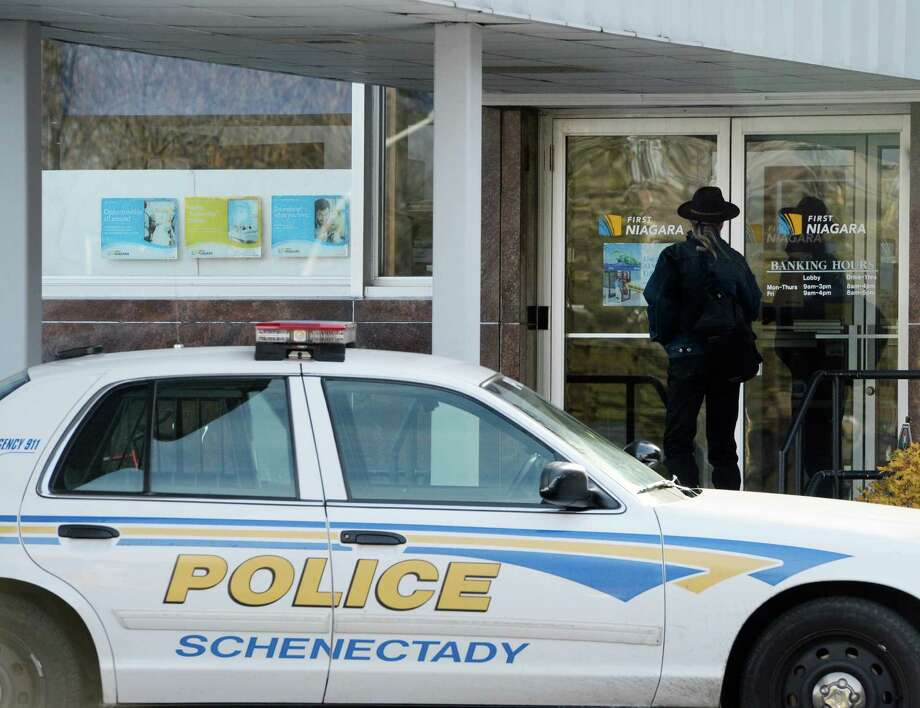 A patron enters the rear entrance of the First Niagara Bank in Shenectady, N.Y. Nov 20, 2012 shortly after the bank was robbed.  The subject is still at large as Schenectady Police investigate.    (Skip Dickstein/Times Union) Photo: Skip Dickstein