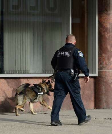 A Schenectady police K-9 unit starts a track outside the front entrance of the First Niagara Bank in Shenectady, N.Y. after a robbery occurred early afternoon Nov 20, 2012.    (Skip Dickstein/Times Union) Photo: Skip Dickstein