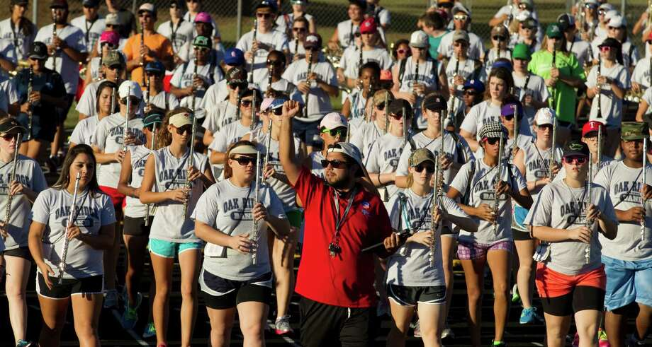 Albert Vela, center in red, leads the Oak Ridge Marching Band around the school's track while preparing for the Macy's Thanksgiving Day Parade. To get ready for the 2 1/2 mile route, the band marches around the school's track the same distance each day.  ( Brett Coomer / Houston Chronicle ) Photo: Brett Coomer, Houston Chronicle / © 2012 Houston Chronicle