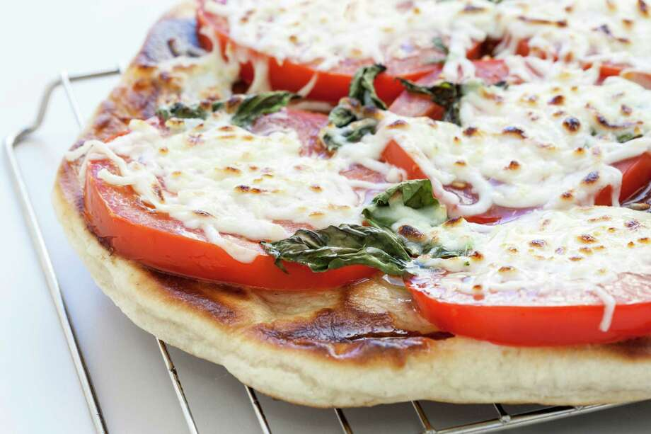 Grilled Margherita Pizza can be cooked outdoors or indoors. Photo: Michael Paulsen, Staff / Houston Chronicle