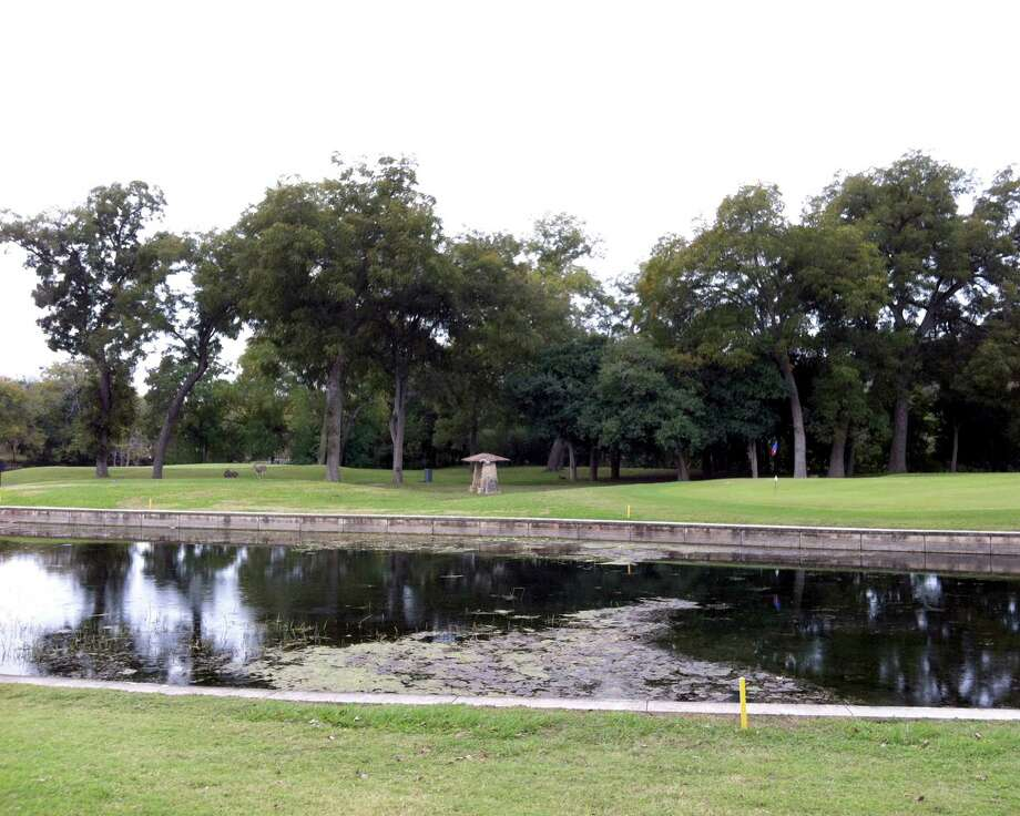 A branch of the Comal River at Landa Park Golf Course in New Braunfels protects the front of the No. 4 green (right) and No. 2 green (beyond trees on left).
