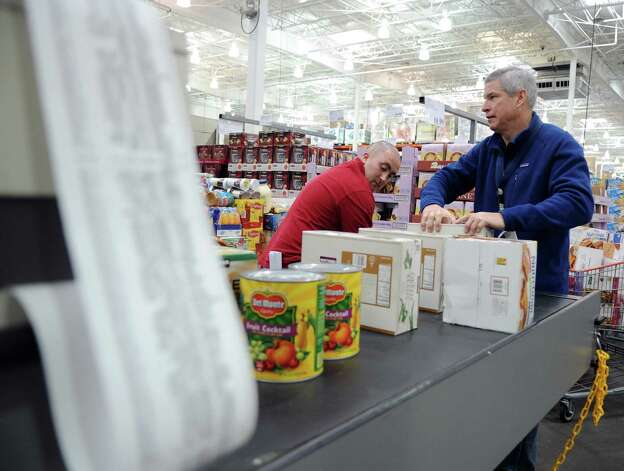 As the reciept gets longer, Priceline CEO Jeff Boyd loads food donations onto a conveyor belt to be checked out at Costco in Norwalk on Tuesday, November 20, 2012. Priceline donated 19,404 pounds of food to the Food Bank of Lower Fairfield County. Photo: Lindsay Niegelberg / Stamford Advocate