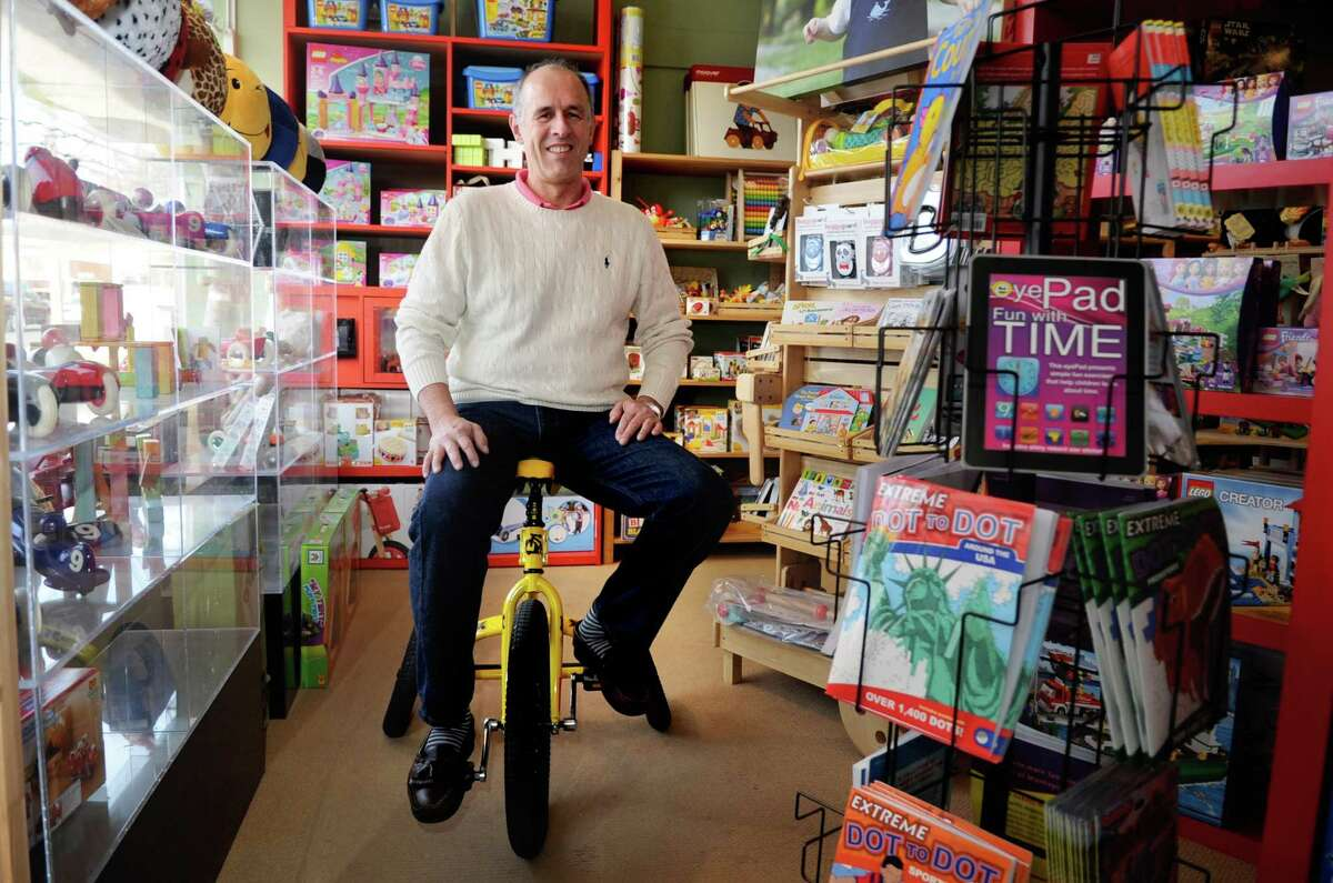 Bill Jensen, owner of Darien Toy Box, poses for a photo while sitting on a CycoCycle on Tuesday, November 20, 2012.