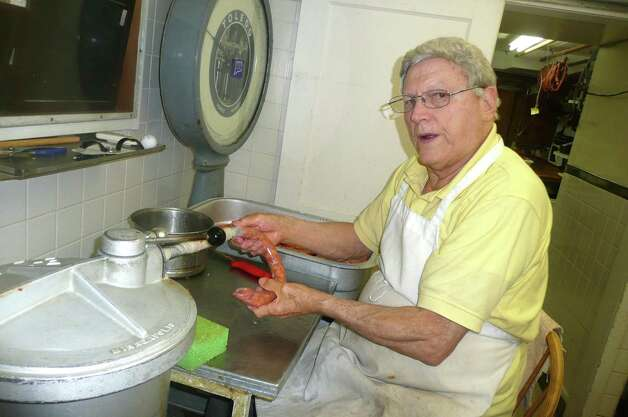 "Peter ""Mac"" Scarpelli has been making sausages the old-fashioned way for 70 years. Here, he feeds the sausage mixture into a casing. Photo: Anne W. Semmes"