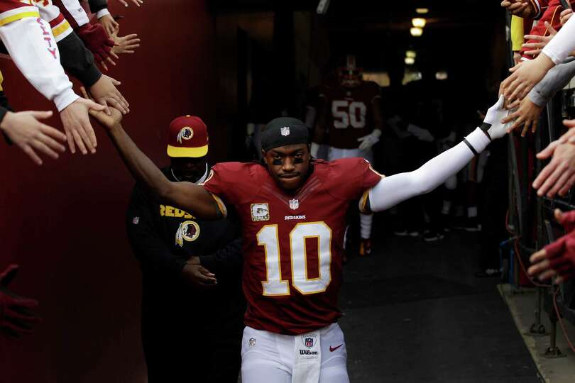 Washington Redskins quarterback Robert Griffin III greets fans as he walks onto the field before the