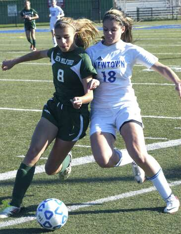 Green Wave sophomore Saige Grazia gets the edge in this close encounter with the Nighthawks during New Milford High School girls' soccer's state class 'LL' semifinal match vs. Newtown in Waterbury. Nov. 17, 2012 Photo: Norm Cummings