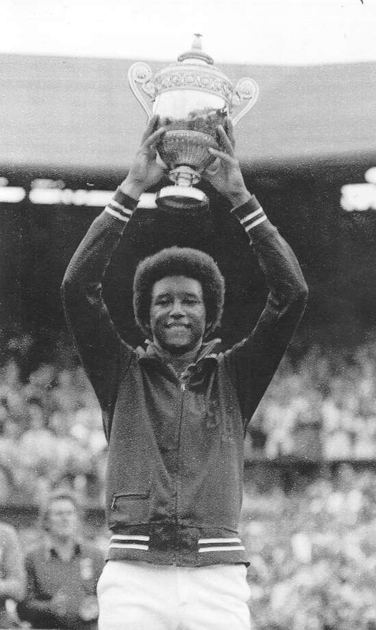 Arthur Ashe holds up his trophy after winning the men's singles finals against Jimmy Connors during the Wimbledon Championship in 1975. Ashe was the first black man to win one of tennis' Grand Slam tournaments. Ashe, a Tennis Hall-of-Famer and human rights advocate, died in New York at age 49 on February 6, 1993. Photo: ASSOCIATED PRESS / EXPRESS-NEWS FILE PHOTO