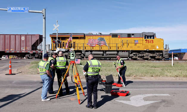 Members of the Midland Police Department collect data during a National Transportation Safety Board sight distance test, Tuesday Nov. 20, 2012 in Midland, Tx., at the intersection of the Union Pacific railroad tracks on South Garfield Street, near West Industrial Avenue where a Union Pacific train struck a parade float at 4:36 p.m. Thursday Nov. 15, 2012, killing four veterans injured in combat. Photo: Edward A. Ornelas, San Antonio Express-News / © 2012 San Antonio Express-News