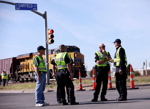 Members of the Midland Police Departmant talk with a National Transportation Safety Board official a National Transportation Safety Board sight distance test, Tuesday Nov. 20, 2012 in Midland, Tx., at the intersection of the Union Pacific railroad tracks on South Garfield Street, near West Industrial Avenue where a Union Pacific train struck a parade float at 4:36 p.m. Thursday Nov. 15, 2012, killing four veterans injured in combat. Photo: Edward A. Ornelas, San Antonio Express-News / © 2012 San Antonio Express-News