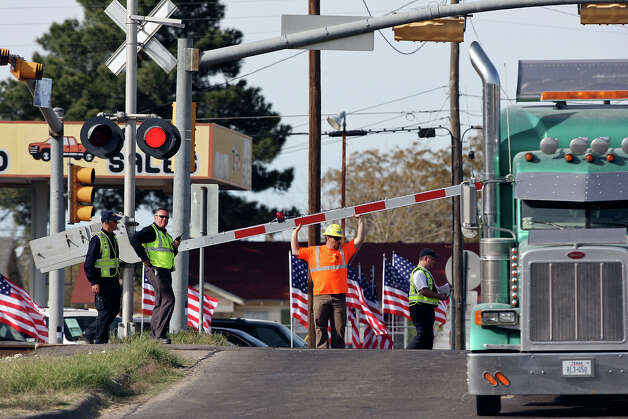 Officials take part in a sight distance test, Tuesday Nov. 20, 2012 in Midland, Tx., at the intersection of the Union Pacific railroad tracks on South Garfield Street, near West Industrial Avenue where a Union Pacific train struck a parade float at 4:36 p.m. Thursday Nov. 15, 2012, killing four veterans injured in combat.    National Transportation Safety Board employees perform a site distance test, Tuesday Nov. 20, 2012 in Midland, Tx., at the intersection of a crash between a parade float and a Union Pacific train that killed four veterans injured in combat. At 4:36 p.m. Thursday Nov. 15, 2012, an eastbound UP train plowed into a Smith Industries flatbed trailer, carrying a dozen injured veterans, their spouses and two escorts in a parade. Photo: Edward A. Ornelas, San Antonio Express-News / © 2012 San Antonio Express-News