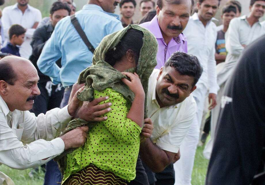 A Pakistani police officer and a Christian volunteer escort a young Christian girl accused of blasphemy to a waiting helicopter after her release from prison in September.  A court ordered the charges dropped on Tuesday. Photo: Anjum Naveed, STR / AP
