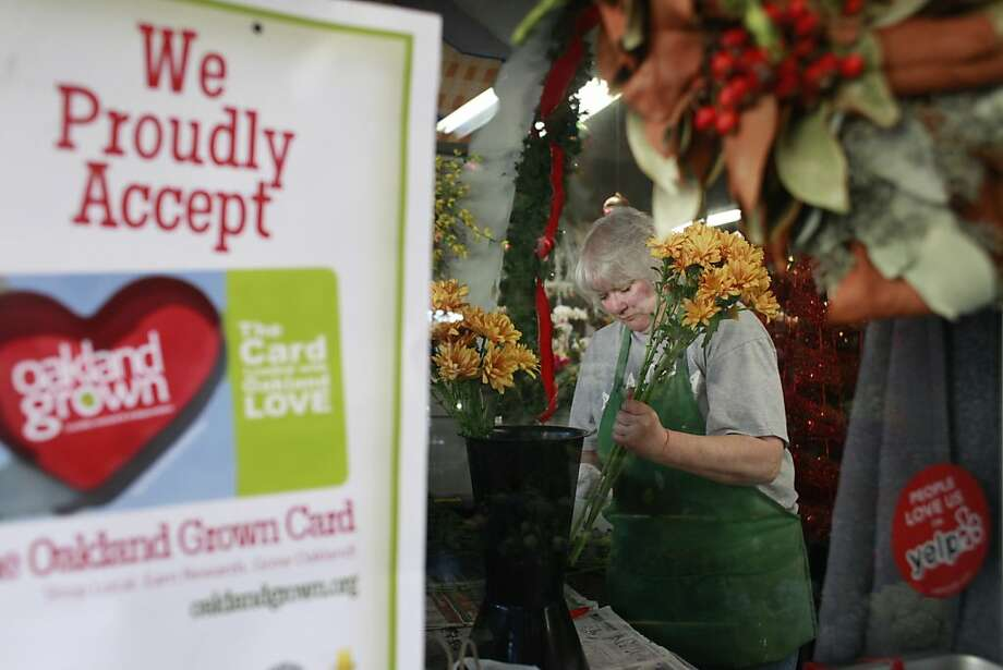 Jeannette Tregea helps a customer at J. Miller Flowers and Gifts, part of the Oakland Grown program.