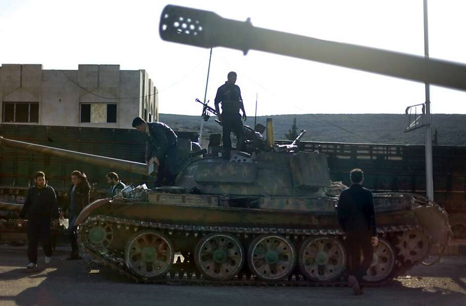 Syrian fighters check a tank they took after storming a military base in Aleppo, Monday, Nov. 19, 2012. Photo: Khalil Hamra, Associated Press