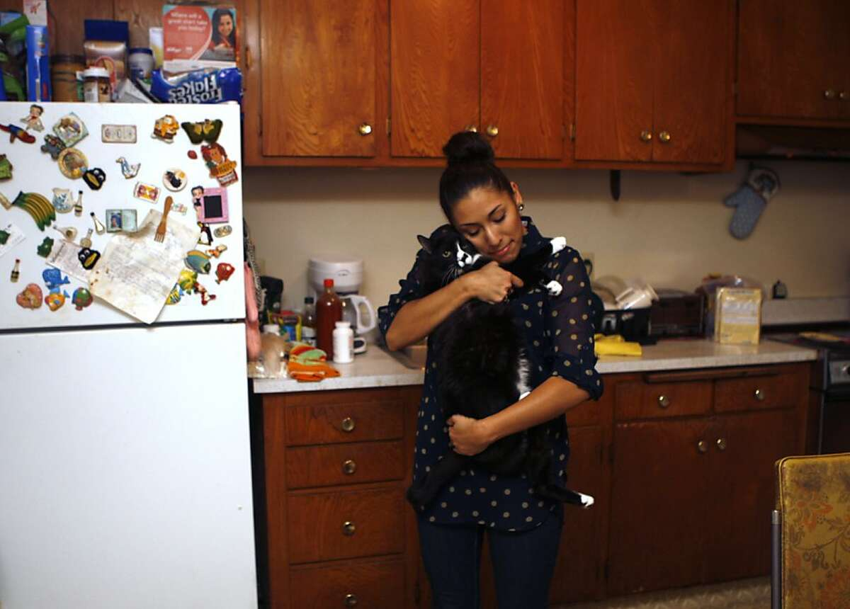 Roommate Martha Gama hugging Betty's fourteen year old cat Bongo at home in San Leandro, Calif., on Monday, November 19, 2012.