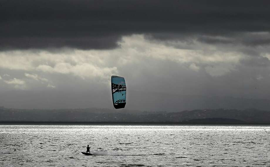 The gray sky doesn't deter a kiteboarder, above, at Crown Memorial State Beach in Alameda while a beachside jogger lopes toward a patch of blue sky. Photo: Michael Macor, The Chronicle
