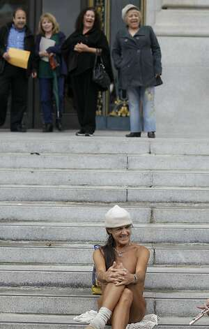 A naked protester sits on the steps of City Hall in San Francisco, Tuesday, Nov. 20, 2012. San Francisco lawmakers on Tuesday narrowly approved a proposal to ban public nakedness, rejecting arguments that the measure would eat away at a reputation for tolerance enjoyed by a city known for flouting convention and flaunting its counter-culture image. The 6-5 Board of Supervisors vote means that exposed genitals will be prohibited in most public places, including streets, sidewalks and public transit. (AP Photo/Jeff Chiu) Photo: Jeff Chiu, Associated Press / SF