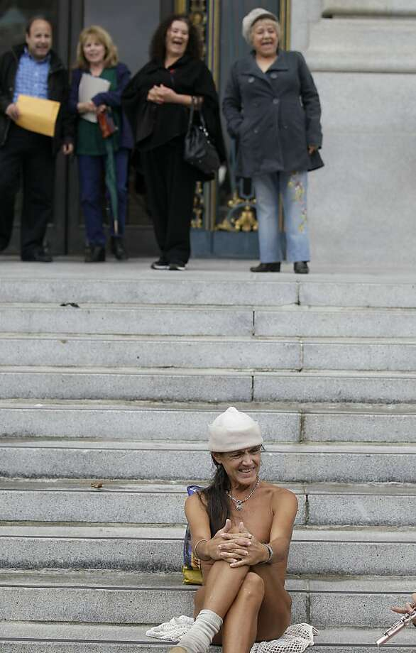 A naked protester sits on the steps of City Hall in San Francisco, Tuesday, Nov. 20, 2012. San Francisco lawmakers on Tuesday narrowly approved a proposal to ban public nakedness, rejecting arguments that the measure would eat away at a reputation for tolerance enjoyed by a city known for flouting convention and flaunting its counter-culture image. The 6-5 Board of Supervisors vote means that exposed genitals will be prohibited in most public places, including streets, sidewalks and public transit. Photo: Jeff Chiu, Associated Press