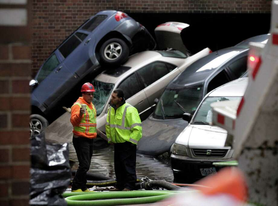 FILE- In this Friday, Nov. 2, 2012, file photo, cars that were uprighted and submerged by Superstorm Sandy remain at the entrance of a subterranean parking garage in New York's Financial District, as the water is pumped out. Thanksgiving travelers who have yet to rent a car in the Northeast are out of luck: Superstorm Sandy has created a shortage. The storm damaged thousands of cars, including those owned by the rental companies. The loss of vehicles was compounded by rising demand. Thanksgiving and Christmas are normally busy rental periods. And lingering mass transit problems caused by Sandy have added to demand. (AP Photo/Richard Drew, File) Photo: Richard Drew