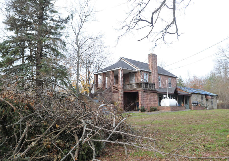 A pile of tree limbs on the front lawn of the Greenwich Emergency Medical Service's location at 1327 King St., that was damaged during Superstorm Sandy last month,Tuesday afternoon, Nov. 20, 2012. The town's Building Department has condemned the structure. Photo: Bob Luckey / Greenwich Time