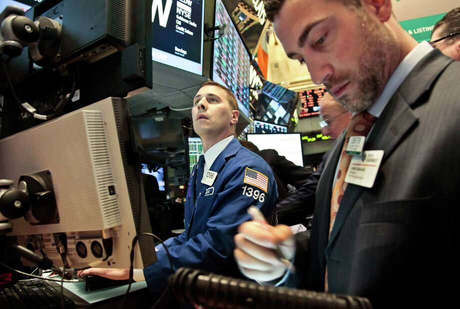 Joseph Mastrolia, left, a trader with Barclays, and Chris Casaliggi, Euronext floor manager, begin early trading on the floor of the New York Stock Exchange on Tuesday, Nov. 20, 2012.  (AP Photo/Bebeto Matthews) Photo: Bebeto Matthews
